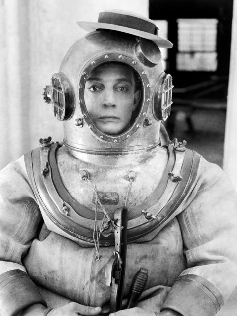 1924: American comedian Buster Keaton (1895-1966) wearing a deep-sea diver suit with his trademark hat perched on top in a scene from his latest film 'The Navigator'.